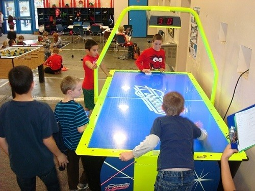 Couple of Kids Playing an Arcade Air Hockey