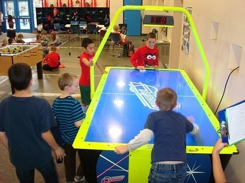 Couple of Kids Playing an Arcade Air Hockey
